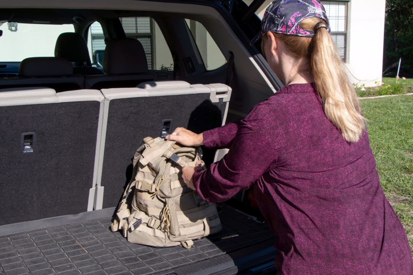 Woman placing get home bag in back of a vehicle