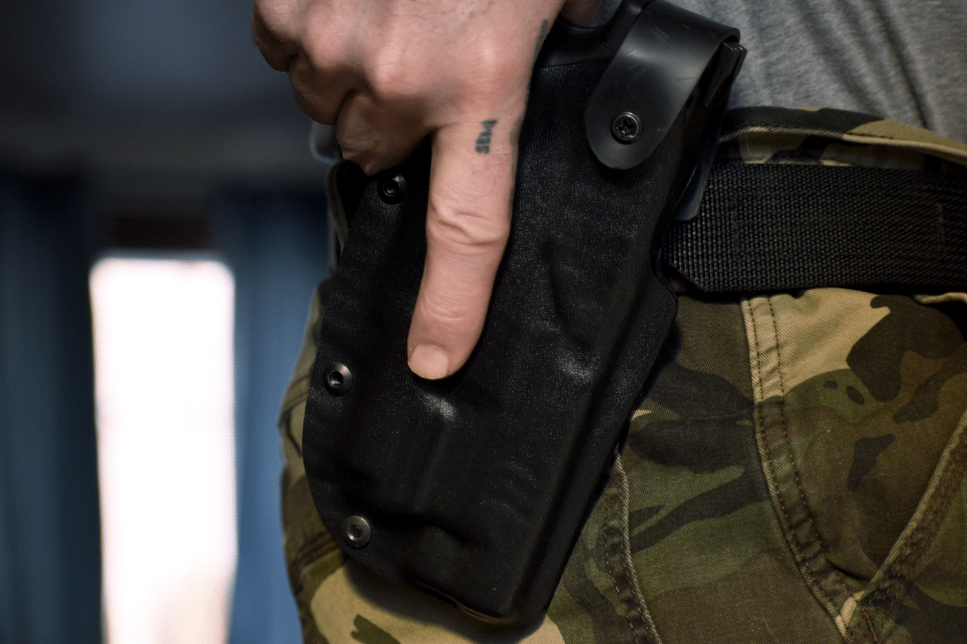 Hand on holster that is attached to EDC belt