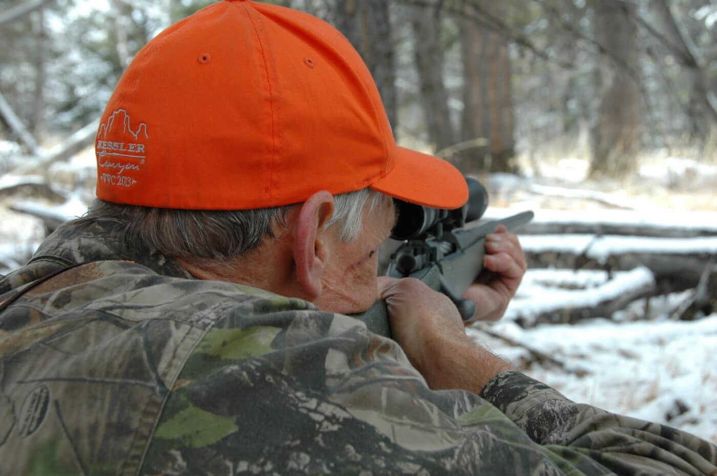 Man using a rifle scope for deer hunting