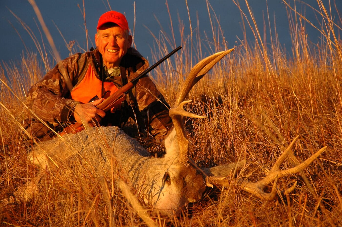 Deer hunter with buck at sunset