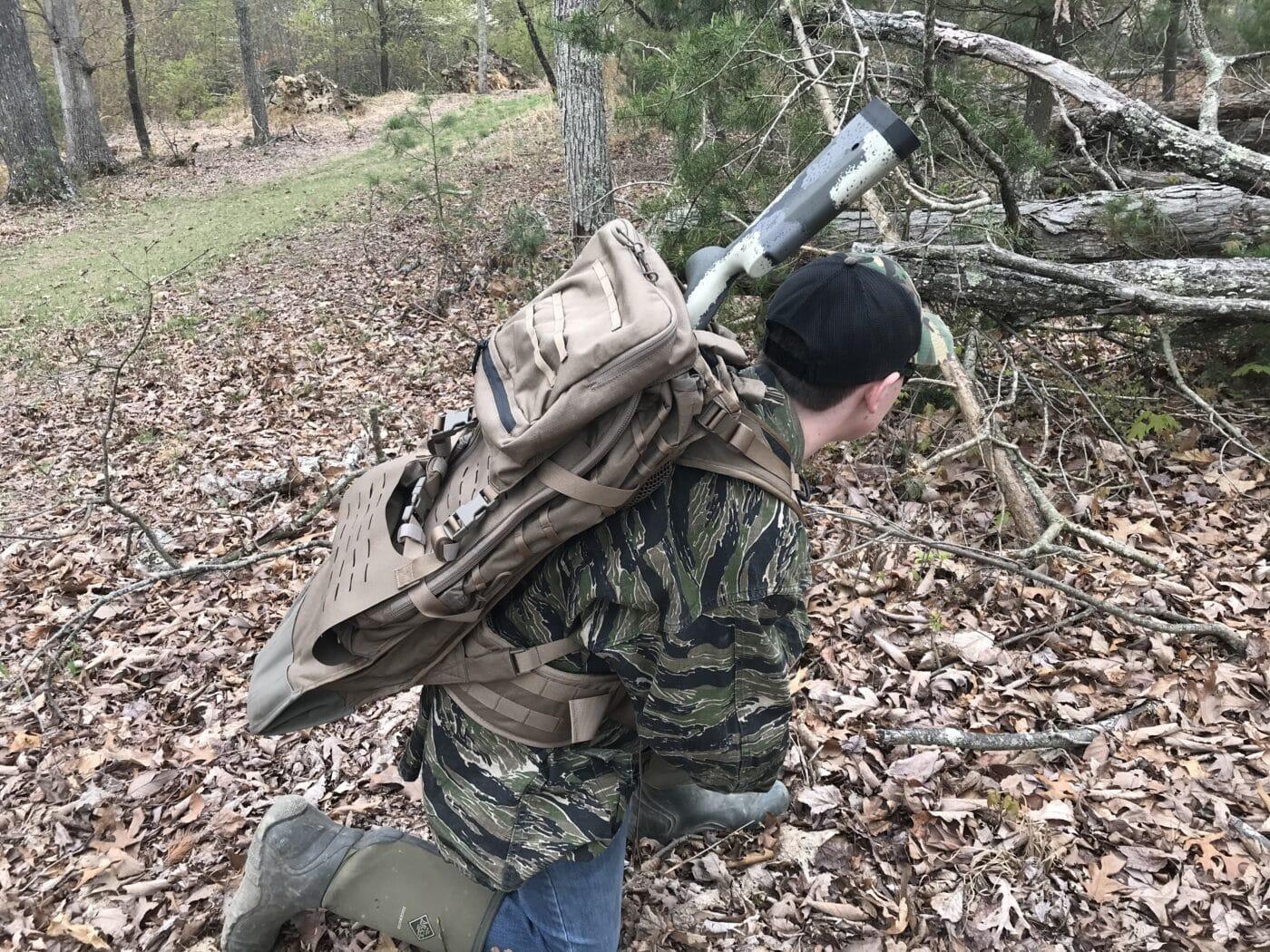 Man carrying a rifle in the Eberlestock Gunslinger II backpack