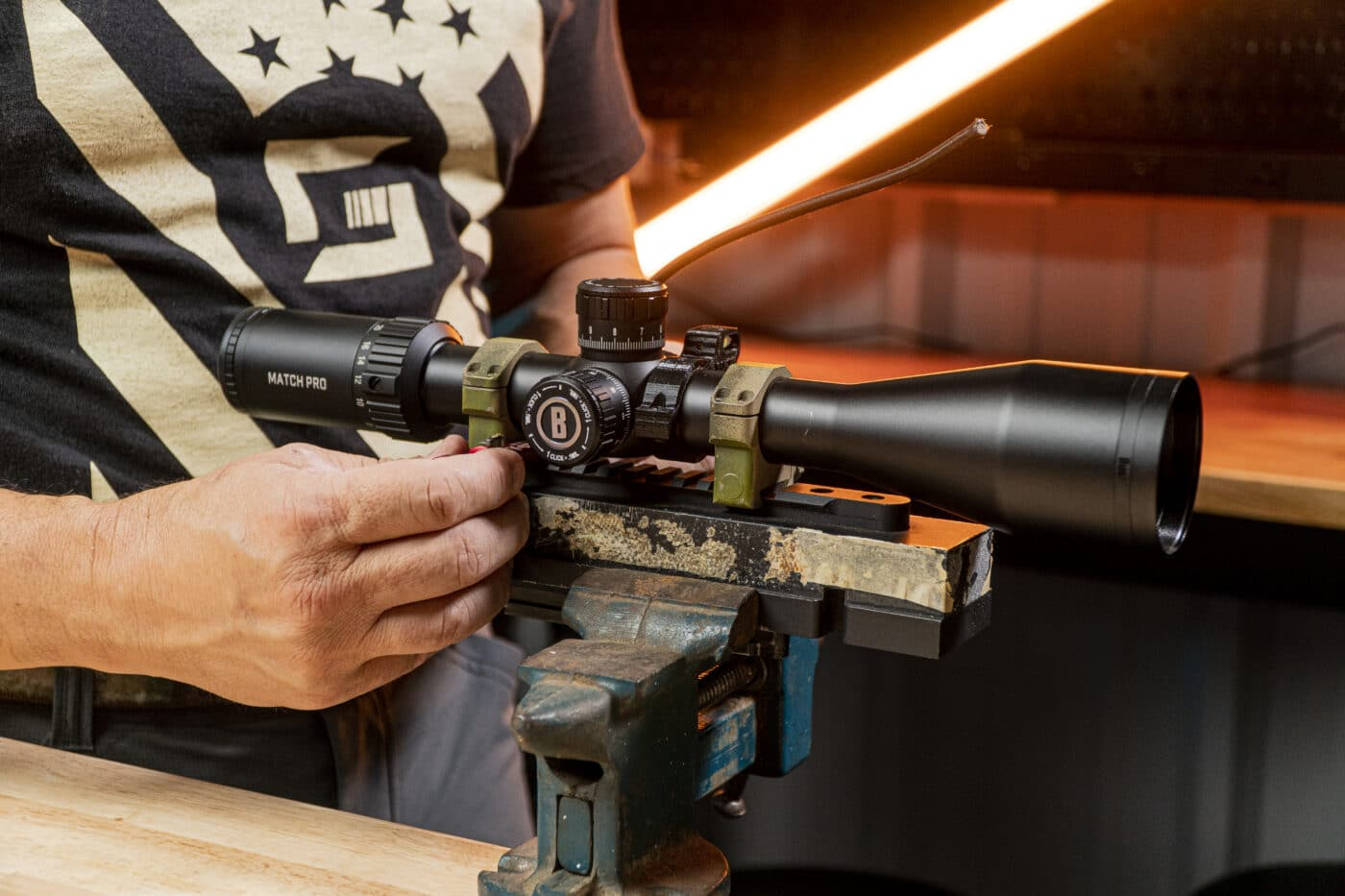 Man using a vice block to level a scope