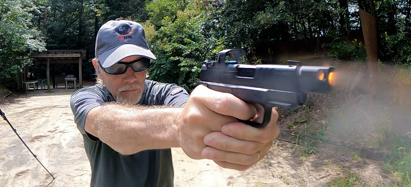 Man tests recoil reduction from Hellcat pistol with compensator