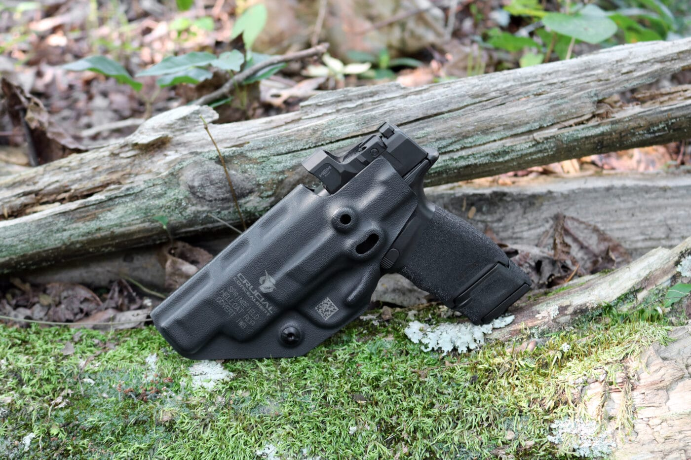 Hellcat pistol in Crucial Concealment Covert holster on moss and wood