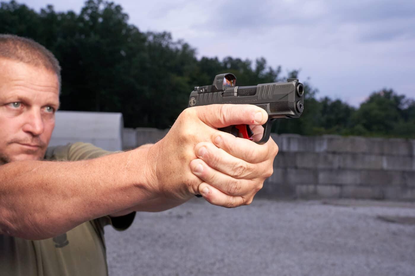 Man shooting custom Hellcat with red dot sights
