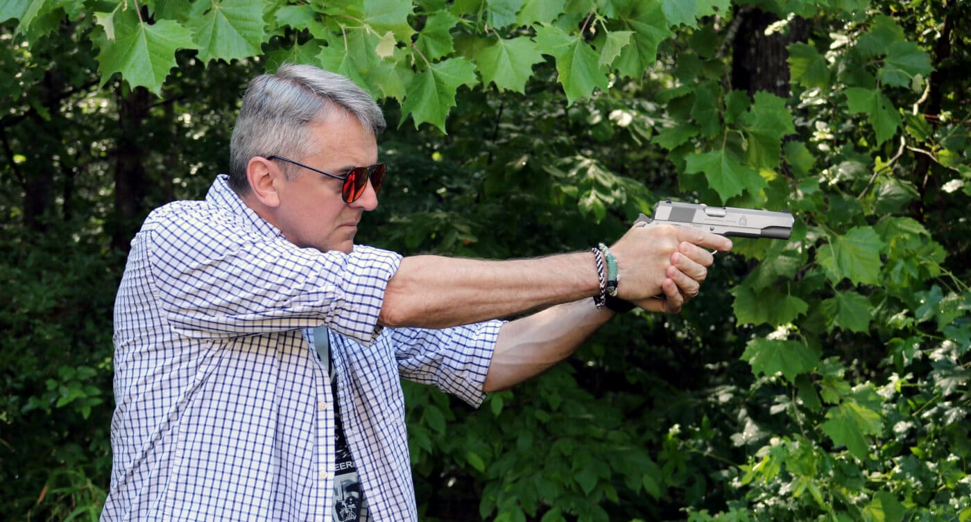 Man shooting a stainless steel 1911 pistol