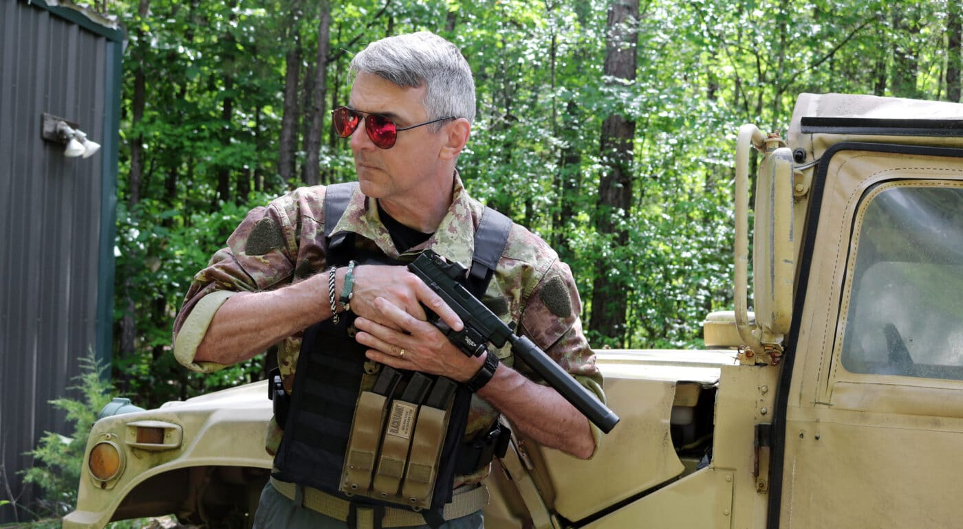 Man holding Springfield XD-M Elite pistol with SureFire suppressor