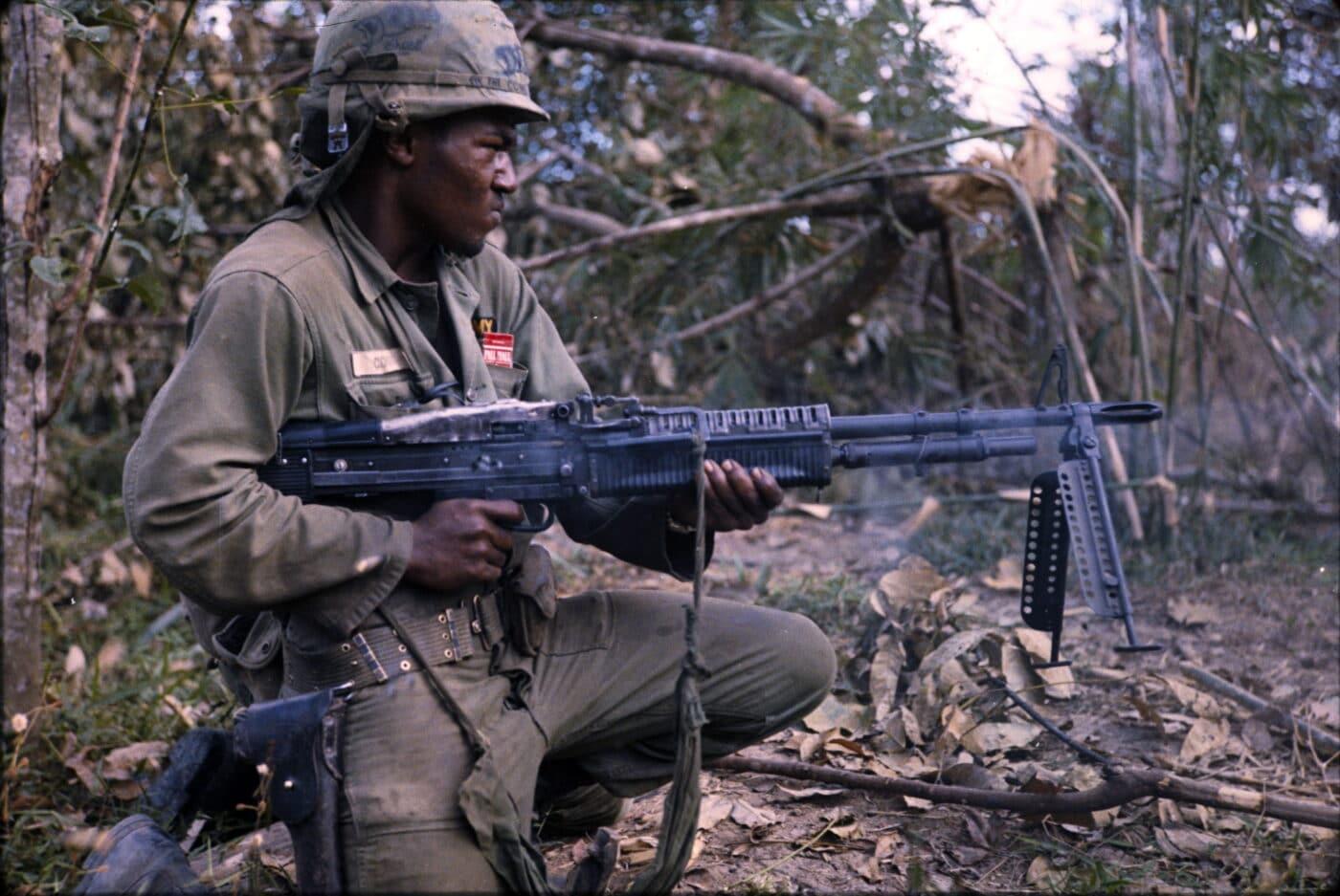 African American army soldier firing M60 in Viet Nam War near Cu Chi