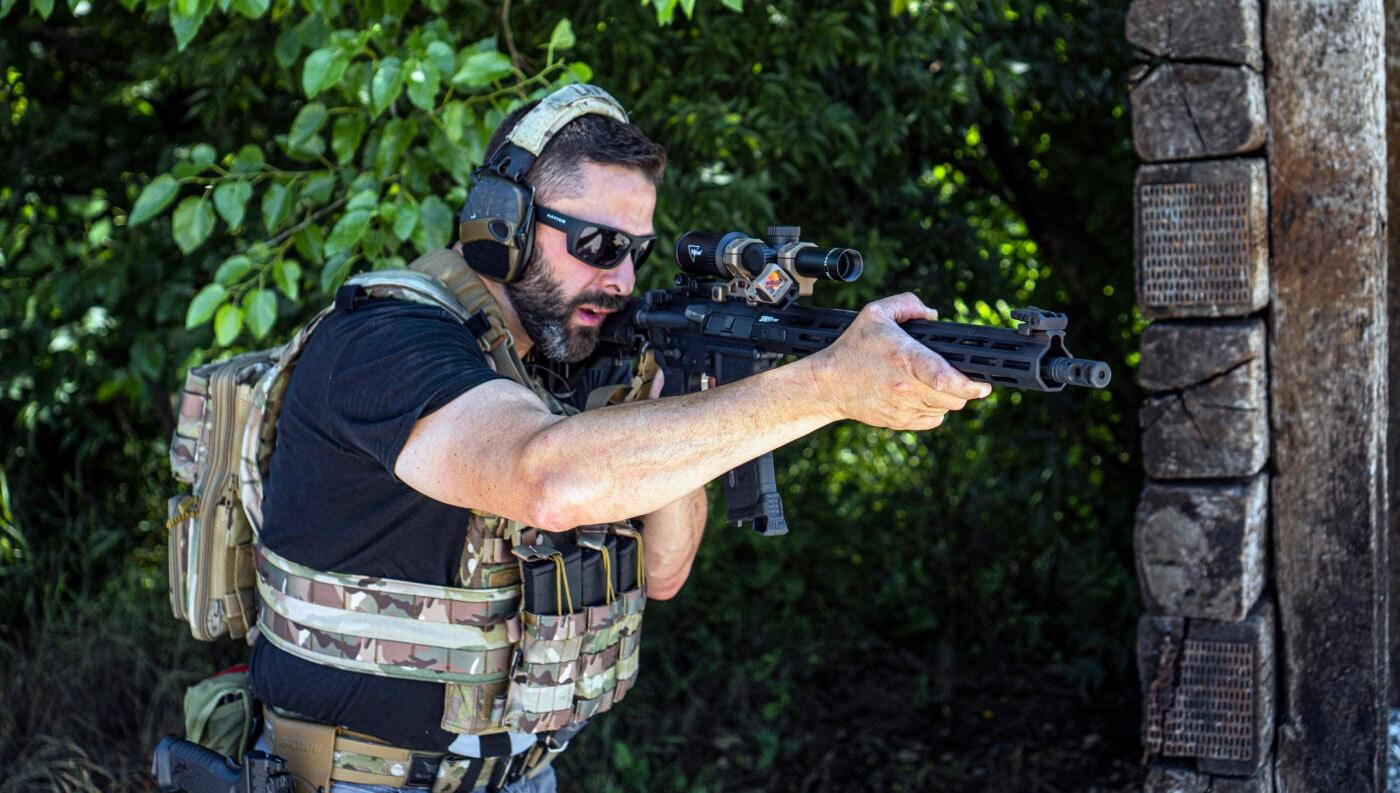Man running an Armageddon gear AR-15 sling on a SAINT rifle