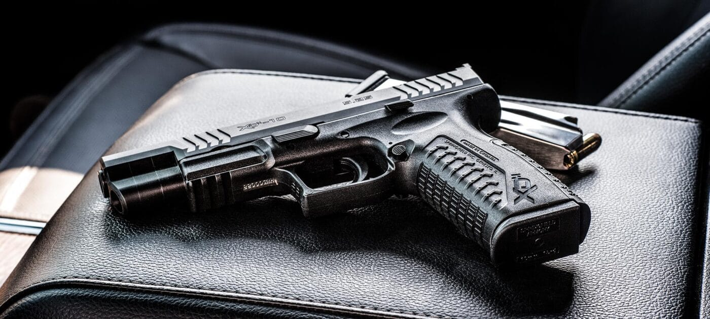 Springfield Armory XD-M 10mm pistol sitting on center console of vehicle