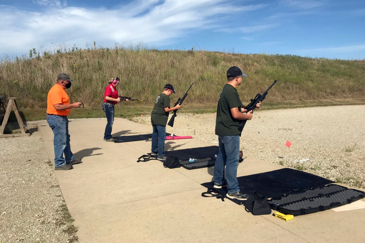 4-H firearms instructor with teens on the range
