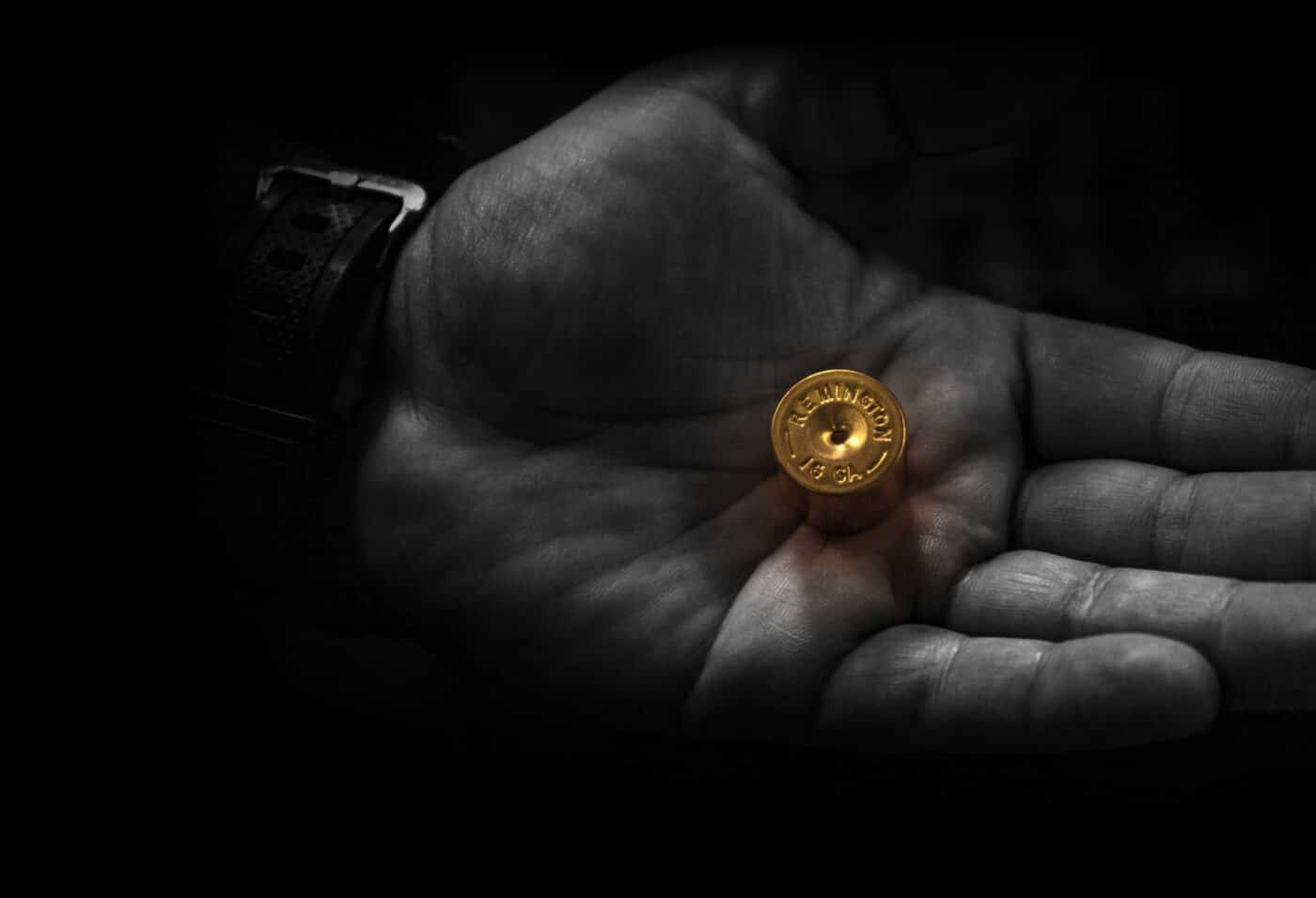 Person's hand holding part of a Remington shotgun shell