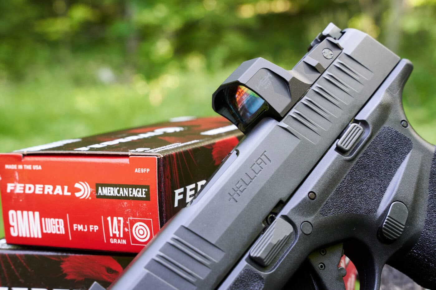 HEX Wasp red dot sight on Hellcat pistol next to ammo