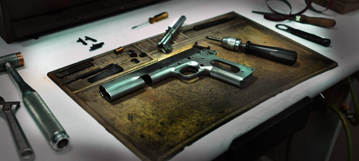 Springfield 1911 pistol disassembled on workbench
